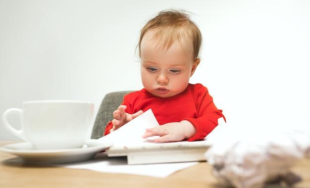 Quantos documentos posso assinar criança menina sentada com teclado do computador moderno ou laptop no estúdio branco.