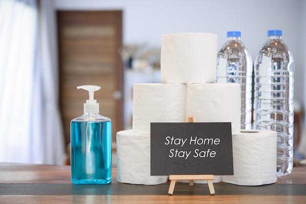 Quarentena doméstica devido a proteção contra coronavírus ou covid-19 com gel para as mãos, rolo de tecido, garrafa de água para beber e placa preta na sala de estar