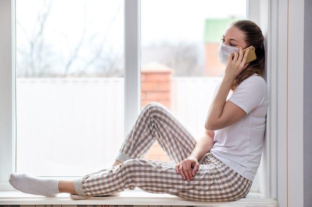 Quarentena em casa. mulher caucasiana em licença médica em máscara protetora médica, falando no telefone. ordena a entrega de alimentos e medicamentos.