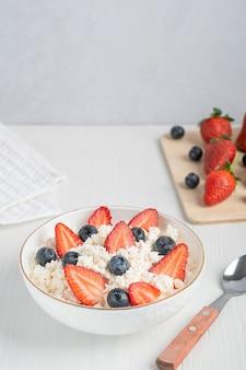 Quark feito de leite fermentado e queijo coalho servido em uma tigela com frutas frescas de verão e colher