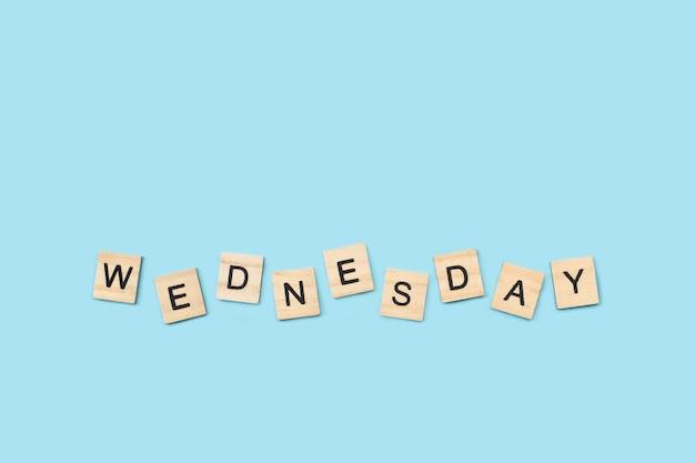 Quarta-feira, escreva com cubos de letras de madeira em um fundo azul claro