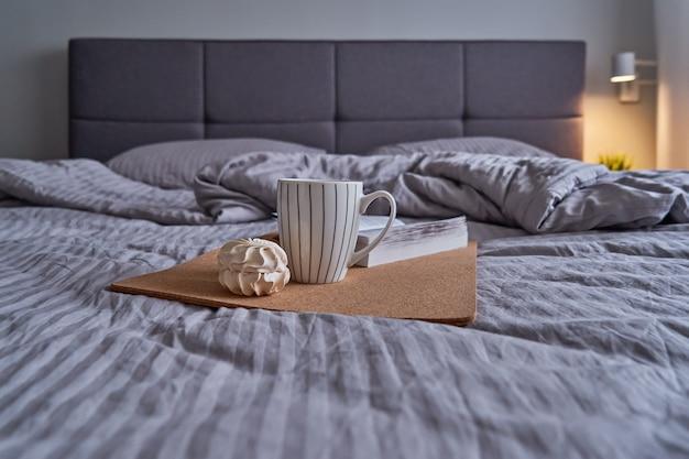 Quarto aconchegante com cama grande e cabeceira macia em cores bege