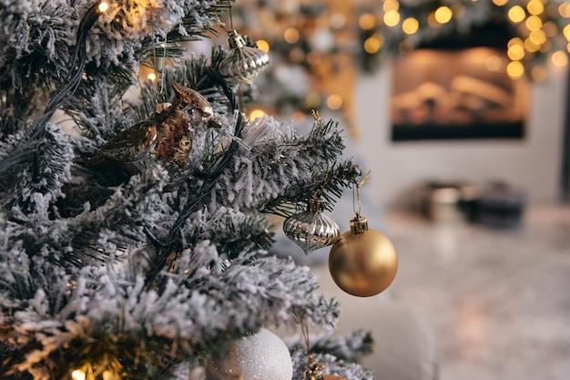 Quarto aconchegante decorado, árvore de natal em neve prateada com brinquedos de bolhas douradas, luzes e presentes embaixo. decoração de casa bonita artesanal diy holdiay. interior de ano novo em um estúdio fotográfico.