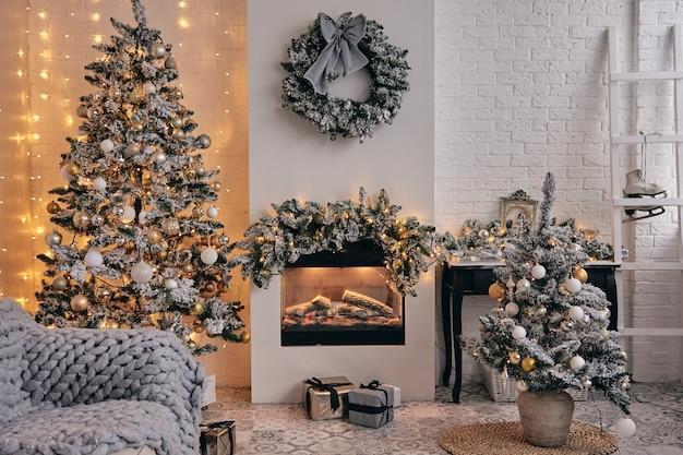 Quarto aconchegante decorado, lareira, árvore de natal em neve prateada com brinquedos de bolhas douradas, luzes e presentes embaixo. decoração de casa bonita feita à mão diy