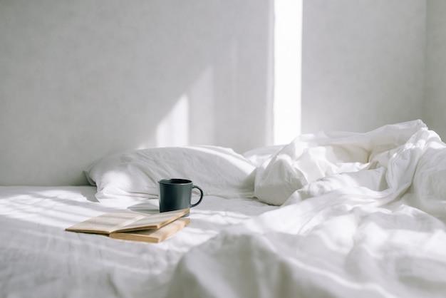 Quarto aconchegante e claro, xícara de café ou chá e um livro aberto na cama.
