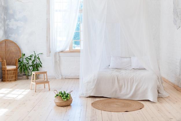 Quarto aconchegante em cores claras, com piso de madeira, uma grande cama de dossel, cadeira de vime e cesta de flores.