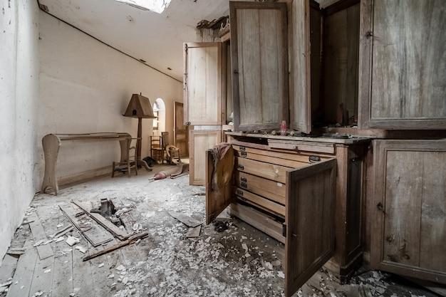 Quarto arruinado com armário aberto