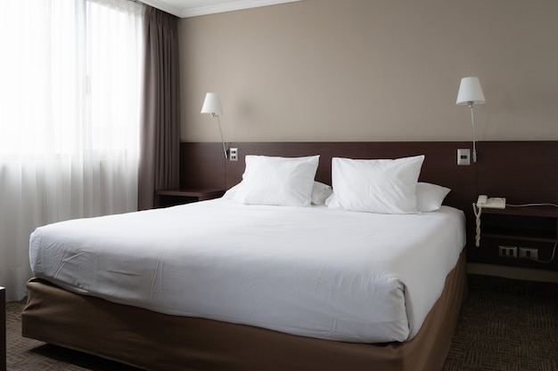 Quarto bem iluminado com cama king-size e abajures nas laterais design de interiores de reserva de hotel