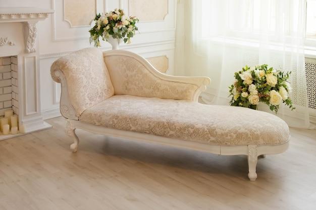 Quarto branco com sofá rosa, flores e lareira perto da janela da sala de estar