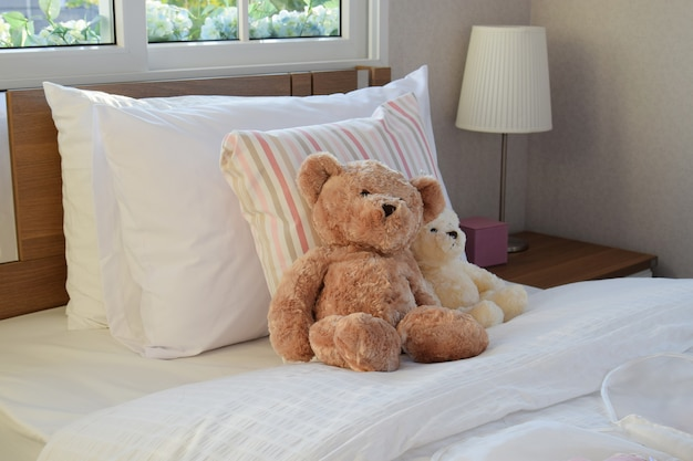 Quarto branco decorativo com almofadas e bonecos na cama