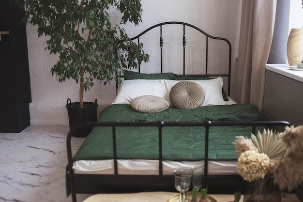 Quarto claro com cama com estrutura de metal preto e árvore de planta doméstica