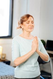 Quarto claro. mulher madura ativa e tranquila em pé com as mãos postas e meditando durante a rotina matinal