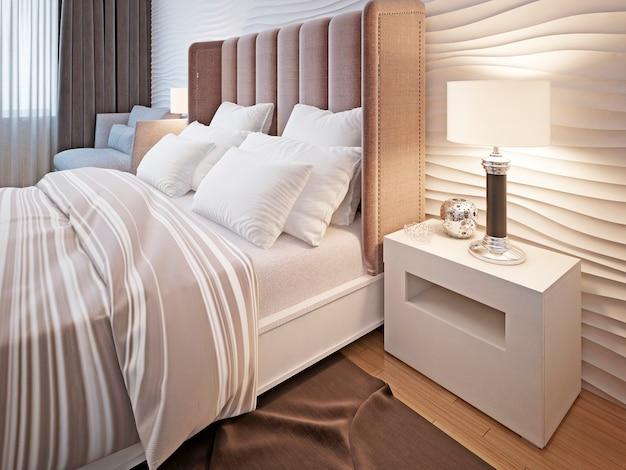 Quarto com cama e roupa de cama e mesa de cabeceira com candeeiro.