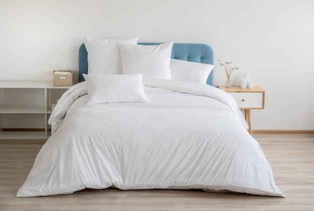 Quarto com cama, roupa de cama branca e mesa de cabeceira.
