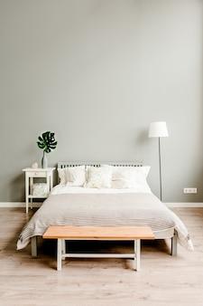 Quarto com móveis de madeira em estilo escandinavo e planta monstera em uma mesa de cabeceira com tronco de árvore