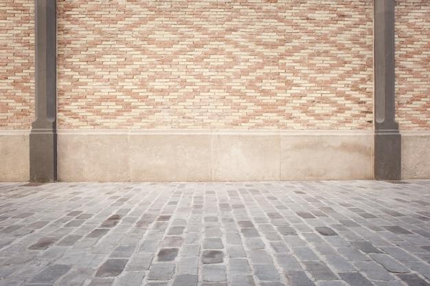 Quarto com parede de tijolos brancos e piso de paralelepípedos