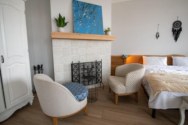 Quarto, conforto. quarto moderno e aconchegante e espaçoso com paredes brancas, lareira grande e pintura