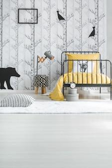 Quarto de criança branco criativo com travesseiro no tapete branco ao lado da cama com roupa de cama amarela