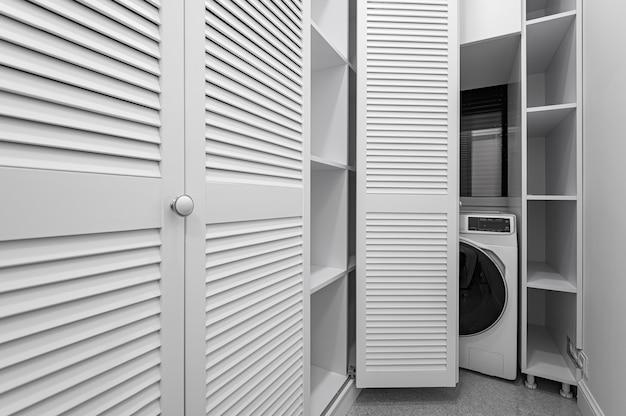Quarto de guarda-roupa branco com máquina de lavar em apartamento novo de luxo