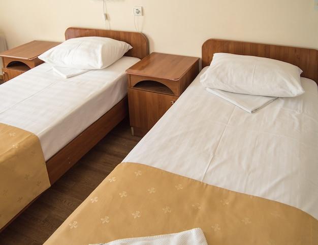 Quarto de hotel com duas camas de solteiro vazias e mesinhas de cabeceira, conceito da hotelaria.