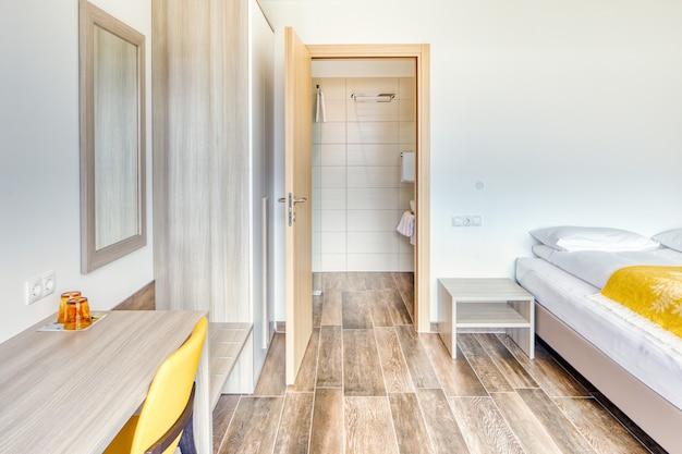 Quarto de hotel minimalista moderno com porta do banheiro aberta, espelho, óculos, cadeira amarela e guarda-roupa