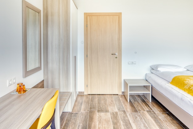Quarto de hotel minimalista moderno com porta do banheiro fechada, espelho, óculos, cadeira amarela e guarda-roupa