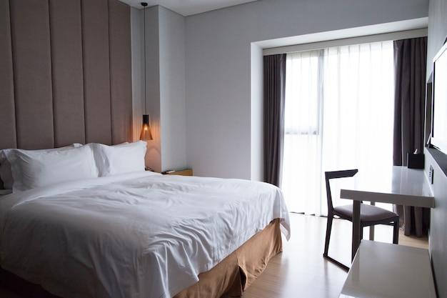 Quarto do hotel com cama de casal, mesa e tv