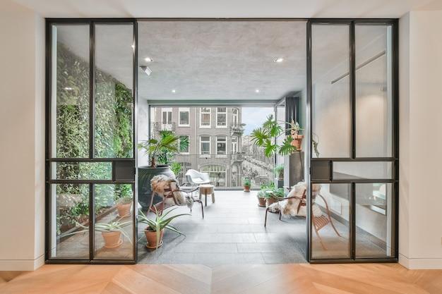 Quarto elegante com varanda com várias plantas e belas cadeiras