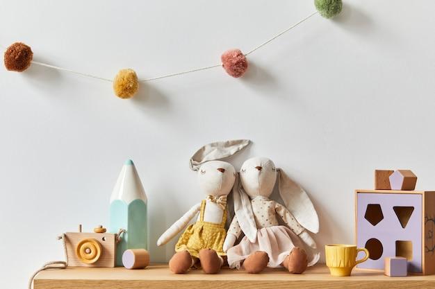 Quarto elegante de bebê recém-nascido escandinavo com brinquedos, animal de pelúcia, câmera fotográfica e acessórios infantis. decoração aconchegante e bolas de algodão penduradas na parede branca. copie o espaço.