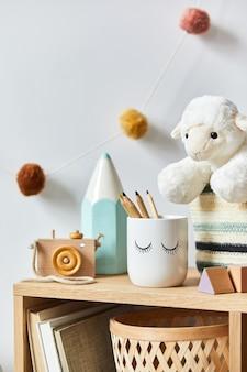 Quarto elegante de bebê recém-nascido escandinavo com brinquedos, animal de pelúcia, câmera fotográfica e acessórios infantis. decoração aconchegante e bolas de algodão penduradas na parede branca. fechar-se.