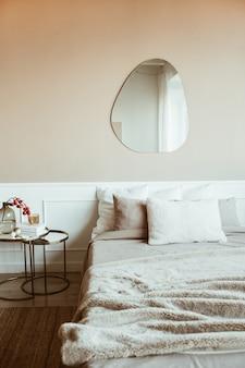 Quarto elegante de cor bege com cama, lençóis, travesseiros, espelho, mesa de cabeceira com buquê de frutas vermelhas, livro