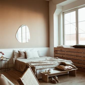 Quarto elegante em bege com cama, lençóis, travesseiros, espelho, mesa de cabeceira com buquê de frutas vermelhas e móveis
