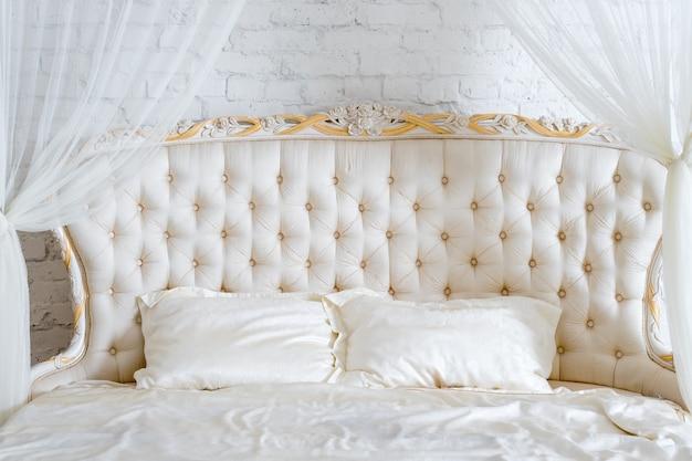 Quarto em cores claras suaves. grande cama de casal confortável no elegante quarto clássico. branco elegante de luxo com design de interiores dourado.