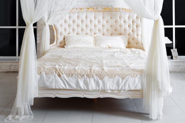 Quarto em cores claras suaves. grande cama de dossel confortável grande no quarto clássico elegante. branco de luxo com design de interiores dourado.