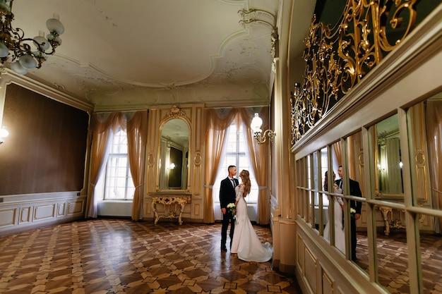 Quarto espaçoso com janelas grandes e muitos espelhos. os recém-casados olham um para o outro. noiva segurando buquê de casamento.