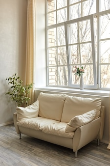 Quarto familiar limpo com sofá de couro branco e janela grande