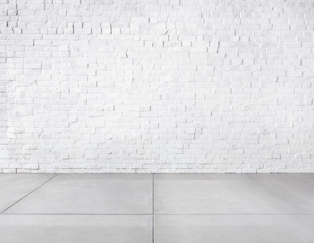 Quarto feito de parede de tijolos e piso de concreto