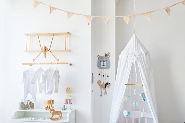 Quarto infantil com interior branco de estilo escandinavo, quarto, creche. berço com â € ¢ dossel. prateleiras e brinquedos em madeira. prateleira de madeira em forma de avião