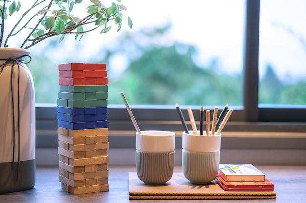 Quarto infantil com lápis e livros sobre a mesa perto da janela.