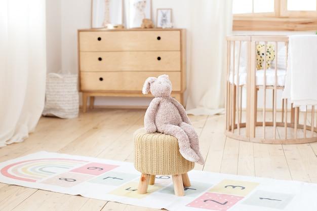 Quarto infantil escandinavo: uma cesta de brinquedos, um coelho de pelúcia sentado em uma cadeira, um berço para uma cama de bebê. interior moderno de um quarto infantil. rústico. copie o espaço. hygge. interior do jardim de infância