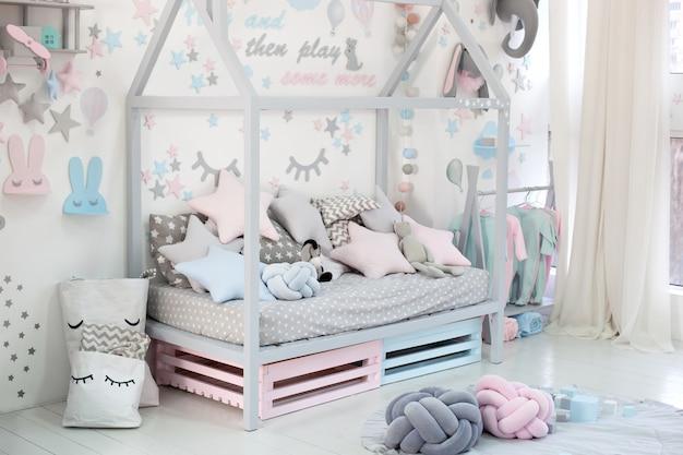 Quarto infantil vazio e acolhedor, com uma parede branca com adesivos, brinquedos, uma cama com almofadas. interior escandinavo de um quarto de crianças. cama de madeira em forma de casa com brinquedos e um cobertor. jardim da infância