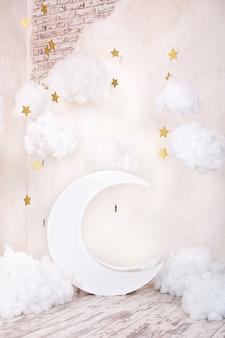 Quarto infantil vintage elegante com uma lua de madeira e nuvens de têxteis. local das crianças para uma sessão de fotos. lua com decoração sonhadora de estrelas e nuvens. quarto infantil vintage elegante com uma lua de madeira