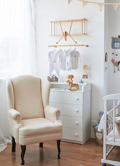 Quarto interior branco de estilo escandinavo, berçário. berço com â € ¢ dossel. prateleiras e brinquedos em madeira. poltrona no quarto das crianças