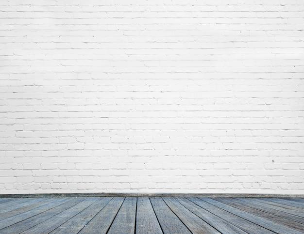 Quarto interior com parede de tijolos brancos e piso de madeira