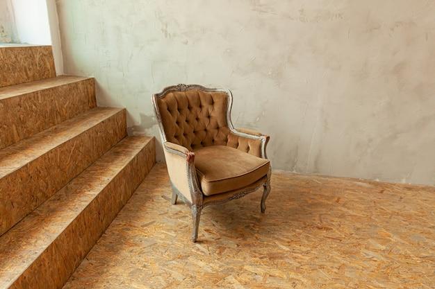 Quarto interior de luxo clássico biege bonito em estilo grunge com poltrona barroca marrom.