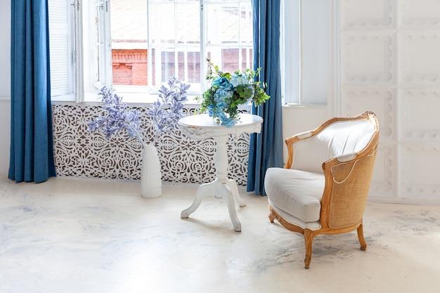 Quarto interior limpo brilhante branco clássico de luxo bonito em estilo barroco com janela grande, poltrona e composição de flores.