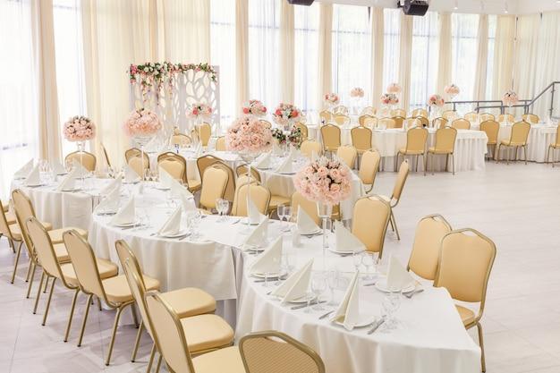 Quarto lindamente decorado com mesas cobertas com flores no restaurante