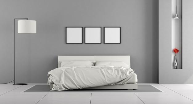Quarto minimalista com cama de casal na parede cinza