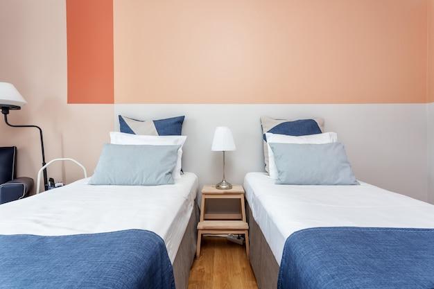 Quarto moderno com travesseiros e cama para turistas. frontalmente.