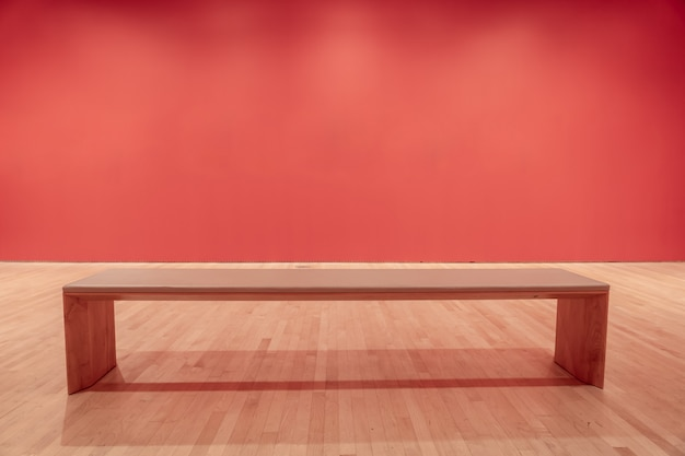 Quarto moderno com uma parede vermelha e um banco